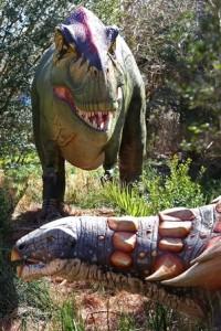 Animatronic Tyrannosaurus rex and Edmontonia exhibited along the garden trail