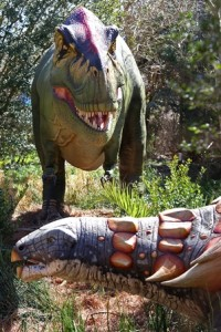 Animatronic Tyrannosaurus rex and Edmontonia exhibited along the garden trail