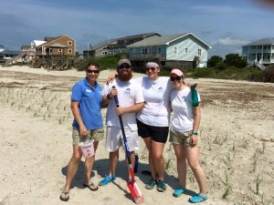 Fort Fisher Aquarium staff planting baby sea oats to help build future sand dunes on Oak Island